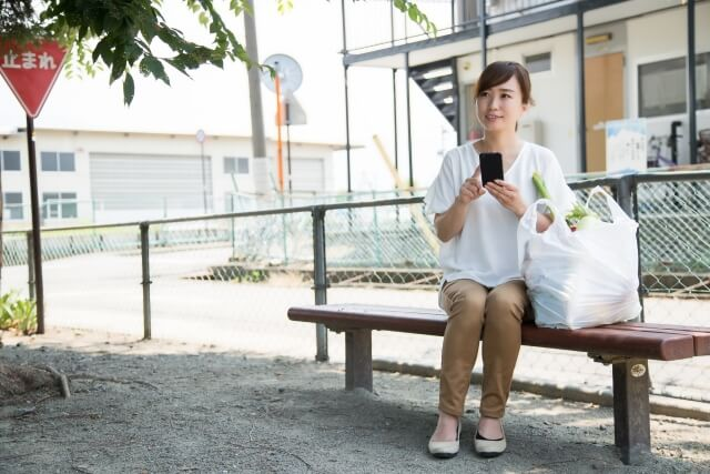 買い物終わりの主婦が公園のベンチで座っている